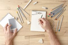 O desenhista tira um esboço em um caderno em uma tabela de madeira stationery Vista de acima imagens de stock royalty free