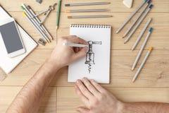 O desenhista tira um esboço em um caderno em uma tabela de madeira stationery Vista de acima fotografia de stock royalty free