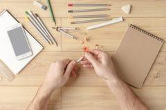 O desenhista tira um esboço em um caderno em uma tabela de madeira stationery Vista de acima fotos de stock