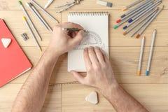 O desenhista tira um esboço em um caderno em uma tabela de madeira stationery Vista de acima fotografia de stock