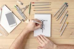 O desenhista tira um esboço em um caderno em uma tabela de madeira stationery Vista de acima imagens de stock