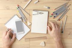 O desenhista tira um esboço em um caderno em uma tabela de madeira stationery Vista de acima foto de stock