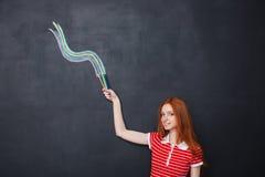 O desenho de sorriso da mulher acena com os lápis coloridos no fundo do quadro-negro Fotos de Stock