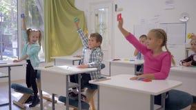 O desenvolvimento de crianças, eruditos levanta formas geométricas nas mãos durante a lição na sala de aula da escola primária vídeos de arquivo