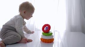 O desenvolvimento do bebê, menino bonito da criança é jogado com a pirâmide educacional do brinquedo na sala brilhante filme