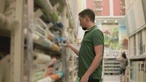 O designer de interiores olha o papel de parede na loja interior, vídeos de arquivo