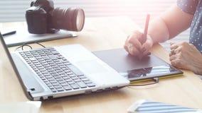 O designer gráfico envelheceu a mulher que usa a tabuleta gráfica digital ao trabalhar no escritório moderno video estoque