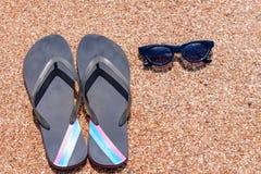 O deslizamento derrama a proteção solar e os óculos de sol em uma praia Fotografia de Stock