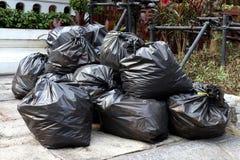 O desperdício loteia a pilha da pilha plástica no parque público à terra do assoalho, muitas dos sacos do preto do lixo despeja a fotos de stock