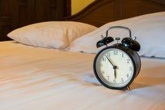 O despertador análogo está na cama branca fotos de stock royalty free