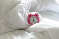 O despertador cor-de-rosa levanta-se seis o'clock na cama na manhã com luz do sol foto de stock