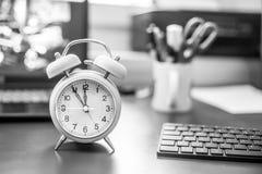 O despertador está estando em uma mesa cinzenta, material do escritório no fundo obscuro fotos de stock royalty free