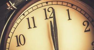 O despertador velho do vintage do grunge está mostrando o movimento do meio-dia ou da meia-noite E filme