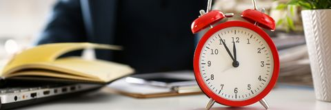 O despertador vermelho mostra o close up atrasado do tempo imagem de stock