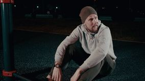 O desportista cansado está descansando após a formação no parque na noite, sentando-se na terra video estoque