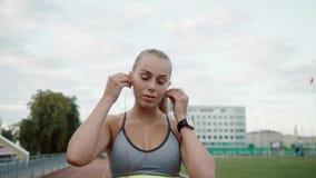 O desportista da menina põe sobre fones de ouvido cor-de-rosa A menina está preparando-se para correr Movimento lento vídeos de arquivo