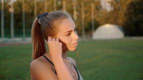 O desportista da menina põe sobre fones de ouvido cor-de-rosa A menina está preparando-se para correr Movimento lento video estoque