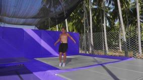 O desportista muscular est? fazendo o salto mortal no ar que salta no trampolim filme