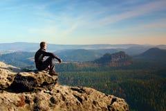 O desportista no preto senta-se no pico da rocha do arenito em impérios da rocha estaciona e olhando sobre o vale enevoado e nevo Foto de Stock Royalty Free