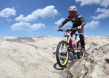 O desportista no sportswear em um Mountain bike monta nas pedras foto de stock royalty free