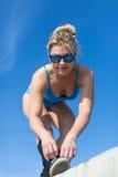 O desportista nos óculos de sol ata acima suas sapatilhas que olham a câmera fotografia de stock
