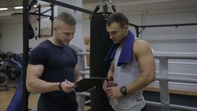 O desportista novo está discutindo treinando resultados seu instrutor no gym vídeos de arquivo