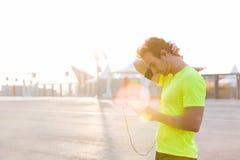 O desportista novo parou na estrada depois que uma corrida ativa ao escutar a música nos fones de ouvido foto de stock