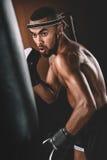 O desportista novo que treina o encaixotamento tailandês com saco de perfuração, luvas de encaixotamento luta o conceito Imagem de Stock Royalty Free