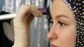 O destaque de Blendable com escova profissional é aplicado à cara do fim modelo acima Modelo da moça com vídeos de arquivo