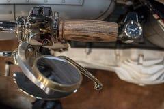 O detalhe da motocicleta de Harley Davidson, do punho de madeira e do espelho dourado foto de stock