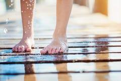 O detalhe de childs molhou os pés no cais, dia de verão ensolarado Fotos de Stock