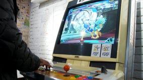 O detalhe de jogadores entrega a interação e o jogo com manches e botões em um jogo de arcada velho em uma sala do jogo Foto de Stock