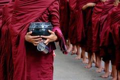 O detalhe de monges budistas aglomera-se e pessoa que guarda uma bacia e um copo Foto de Stock