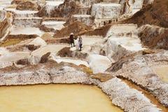 O detalhe de sal ponds com trabalho de povos locais no fundo Imagens de Stock