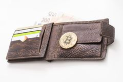 O detalhe de uma carteira de couro aberta com um Bitcoin dourado grande, notas da autorização e cartões e azul de crédito ilumino fotos de stock royalty free