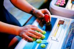 O detalhe nas mãos que guardam o manche e que empurram abotoa-se em uma sala do jogo Fotos de Stock