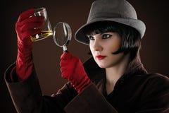 O detetive da mulher examina fotos de stock