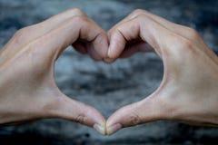 O deus é conceito do amor, mãos que fazem a forma do coração e o fundo de madeira velho, símbolo do amor, manifestação do amor, e foto de stock royalty free