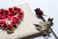 O diário e as rosas do amor murcham no fundo branco da lona fotografia de stock royalty free