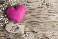 O dia das mulheres felizes na etiqueta do papel marrom com coração cor-de-rosa Fotos de Stock