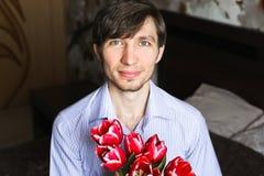 O dia das mulheres, indivíduo com tulipas vermelhas Imagem de Stock Royalty Free