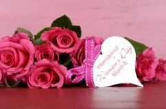 O dia das mulheres internacionais, o 8 de março, as rosas cor-de-rosa com presente etiquetam Imagem de Stock