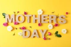 O dia de mãe da inscrição sobre com as rosas no fundo da cor foto de stock