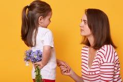 O dia de mãe feliz! A menina bonito da criança felicita sua mãe no feriado e quê-la dar flores Doughter esconde o ramalhete do az imagens de stock royalty free