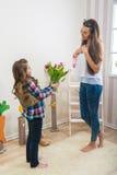 O dia de mãe - a menina dá a sua mamã um ramalhete grande das tulipas, tocando Fotografia de Stock Royalty Free