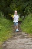 O dia de mãe: rapaz pequeno com flores, fora Imagem de Stock Royalty Free