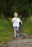 O dia de mãe: rapaz pequeno com flores, fora Imagem de Stock