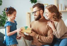 O dia de pai feliz! mam? e filha da fam?lia para felicitar o paizinho e dar o presente imagem de stock royalty free