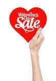 O dia de Valentim e o assunto da venda: Entregue guardar um cartão sob a forma de um coração vermelho com a venda da palavra isol Fotografia de Stock