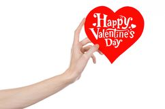 O dia de Valentim e o tema do amor: a mão guarda um cartão sob a forma de um coração vermelho com o dia de Valentim feliz das pal Fotos de Stock